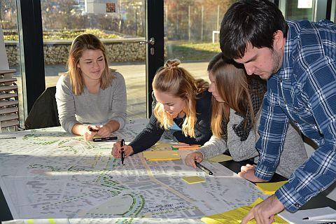 Vier junge Menschen zeichnen einen Plan