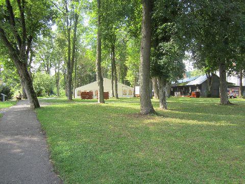 Ein schmaler Weg läuft entlang einer Wiese mit Bäumen