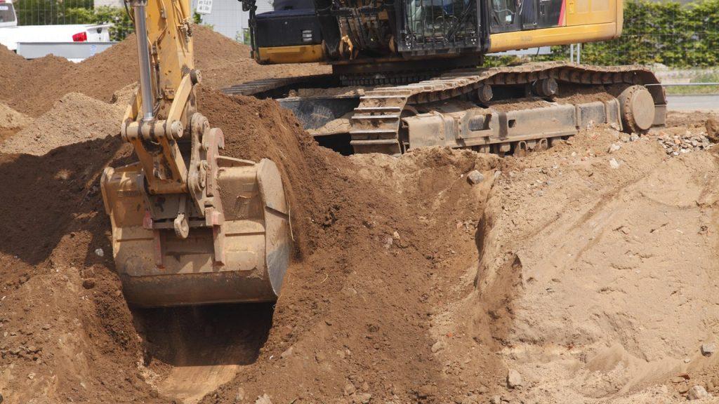Eine Baggerschaufel gräbt erin Loch