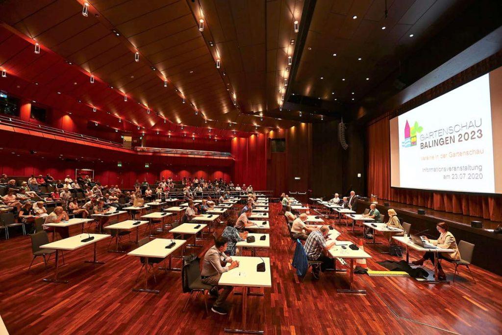 Menschen sitzen verteilt an Schreibtischen in einem großen Saal.
