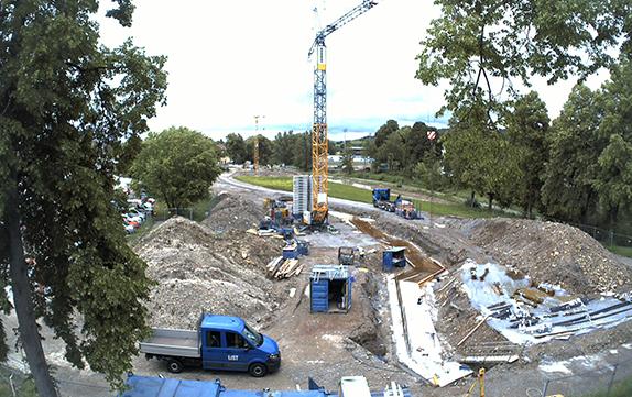Blick von oben auf eine Baustelle mit einem Kran in der Mitte, Baumaterial liegt auf dem Boden.