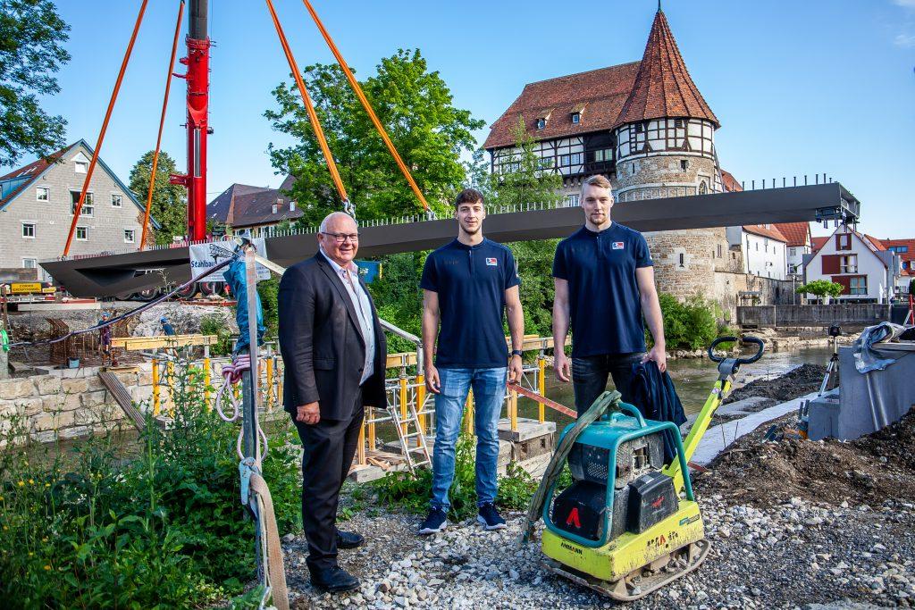 Oberbürgermeister Helmut Reitemann mit zwei HBW Spielern vor der schwebenden Brücke