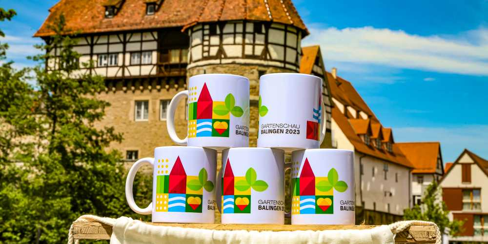 Keramiktassen mit Gartenschau-Logo vor dem Zollernschloss