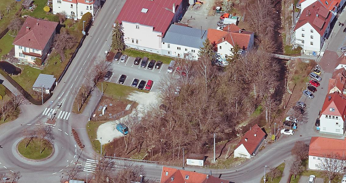 Luftbild von Straßen mit Häusern, einem Kreisverkehr und Parkplätzen