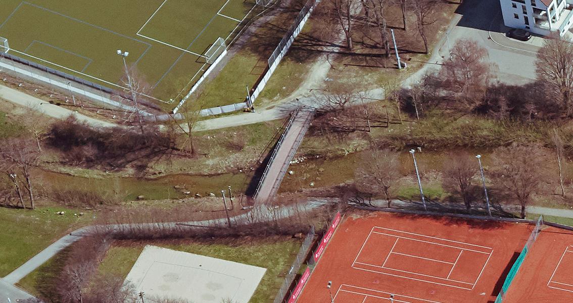 Luftbild von einem Steg über einen Bach, Tennisplätzen und Sportplatz